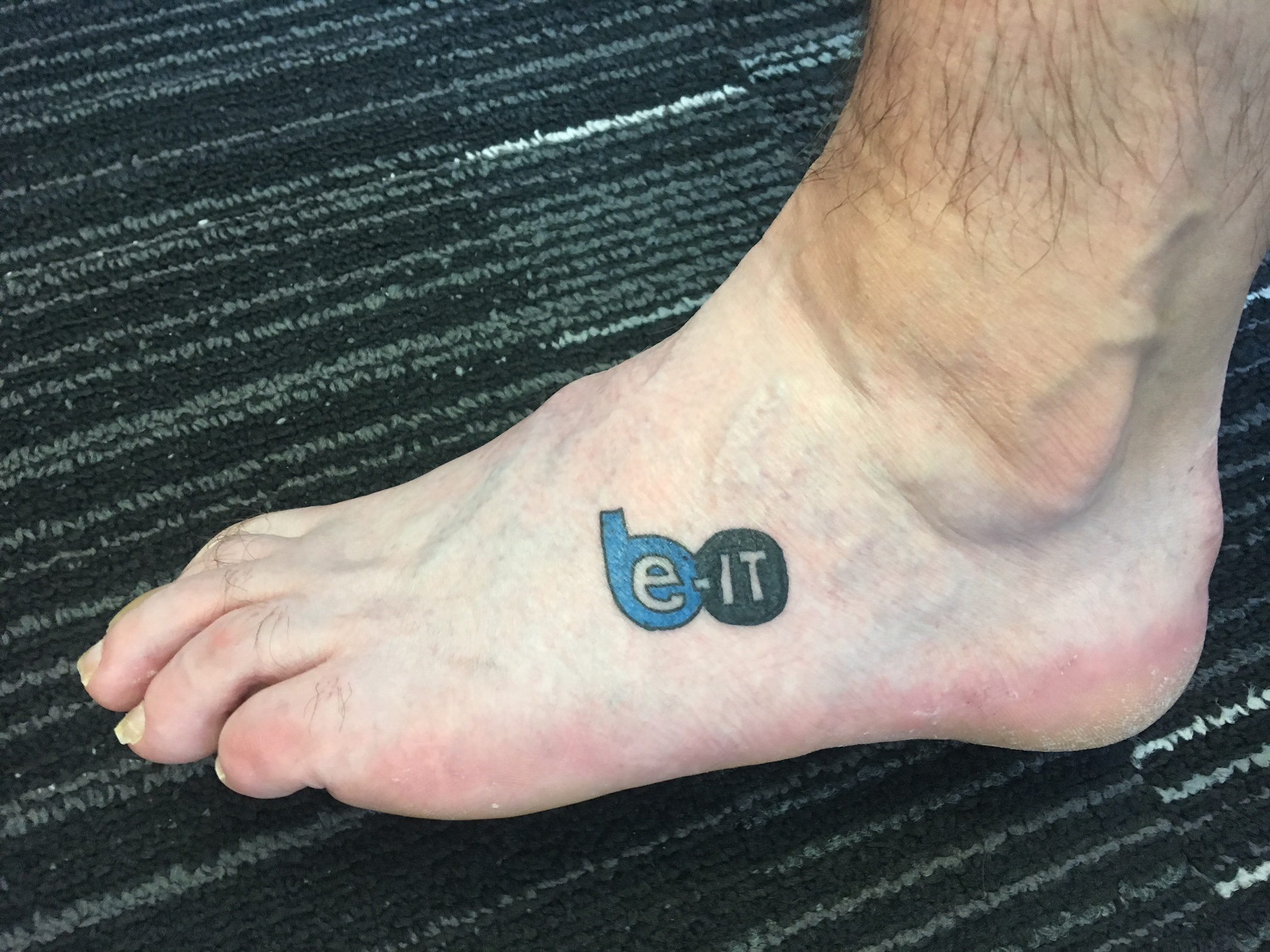 Zander's foot with the Be-IT logo tattoo